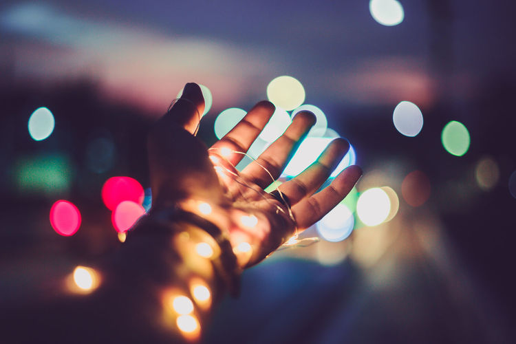 Defocused image of hand holding illuminated lights at night