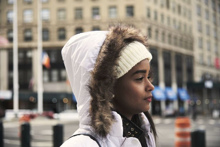 Portrait of young woman looking away in city