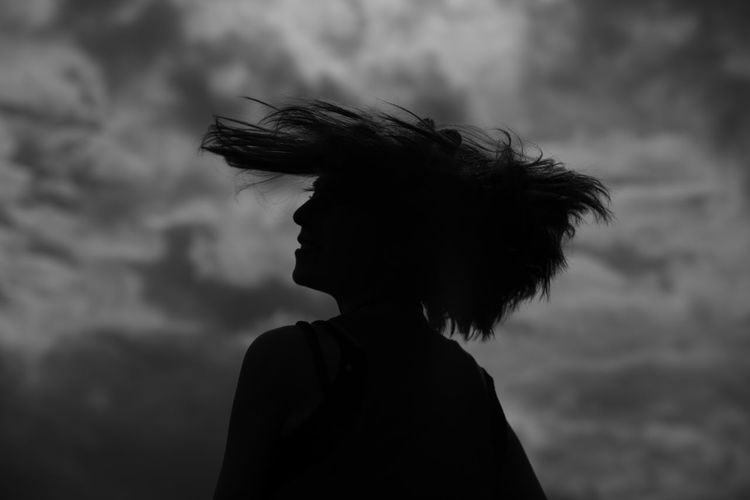 Close-Up Of Silhouette Young Woman Shaking Head Against Cloudy Sky During Sunset