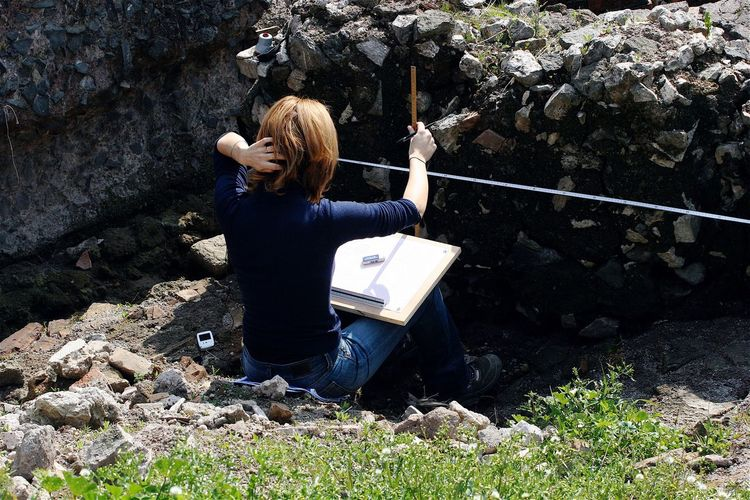 Rear View Of Woman Measuring Rocks While Sitting On Field