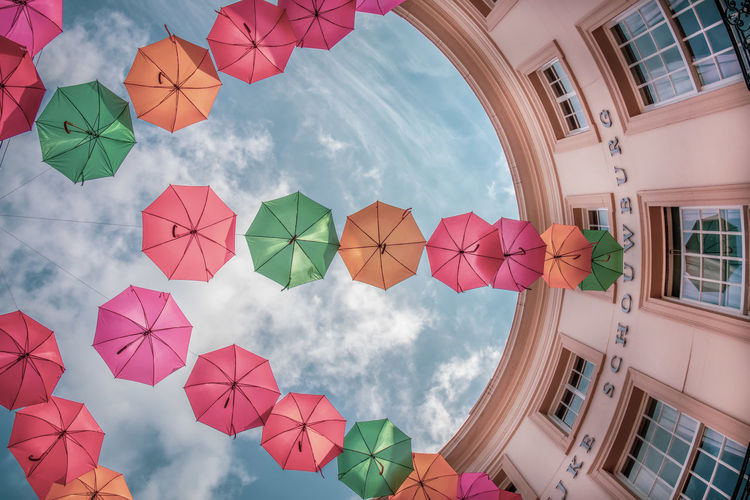 Low angle view of multi colored umbrellas hanging amidst buildings against sky