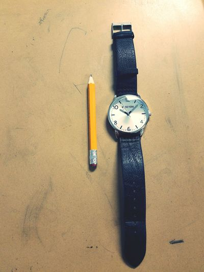 High angle view of pencil and wristwatch