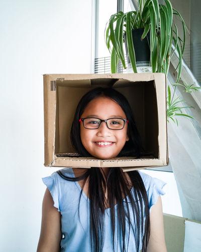 Smiling girl wearing cardboard box