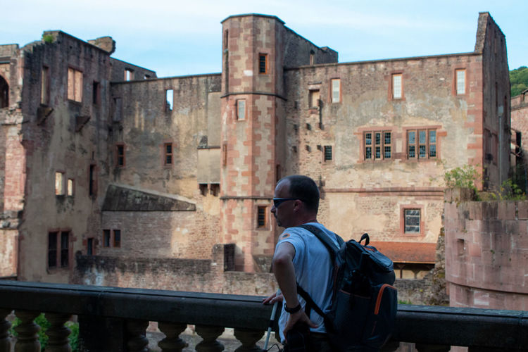 Rear view of man standing by building against sky