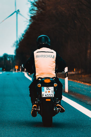 Transportation Road Focus On Foreground Rear View Street City Mode Of Transportation Illuminated Land Vehicle Sign Incidental People Day Outdoors Car Text Men Real People People Motor Vehicle Driving School Motorcycle Motorbike