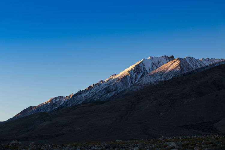 Low Angle View Of Snowcapped Mountain Against Clear Blue Sky