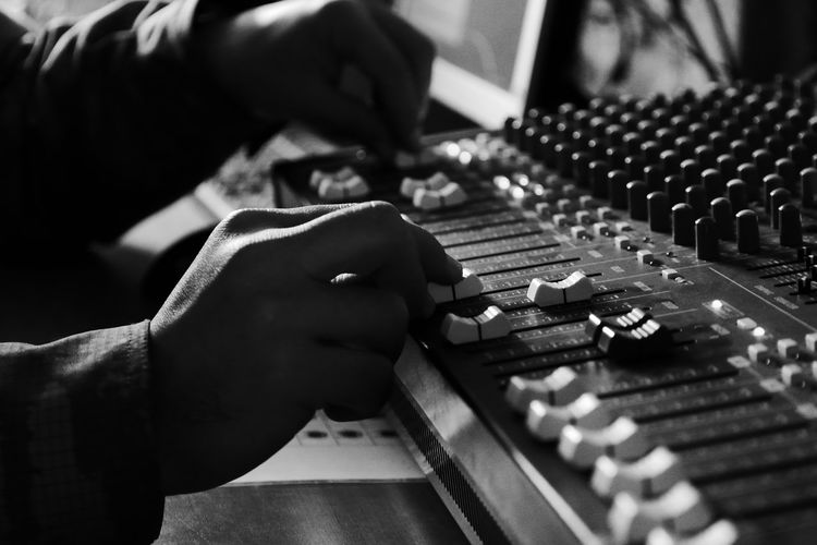 Cropped Hands Of Man Adjusting Sound Mixer Knobs