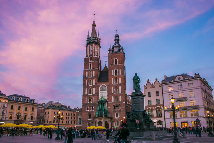 Romantic view of medieval market square of Krakow at dusk in Poland Krakow Poland Sunset Dusk Rynek Główny Basilica Market Square Medieval Medieval Architecture Architecture Religion Religious  Palace Travel Destinations Travel Europe European  Vacations Holiday Winter Statue Sculpture Amazing Romantic Romantic Sky Skyline View Building Exterior Built Structure Building Sky City Place Of Worship Group Of People Crowd Tower Large Group Of People Spirituality Cloud - Sky Belief The Past History Outdoors Spire  Clock Saint Mary Saint