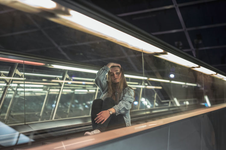 Portrait of woman sitting on escalator in city at night