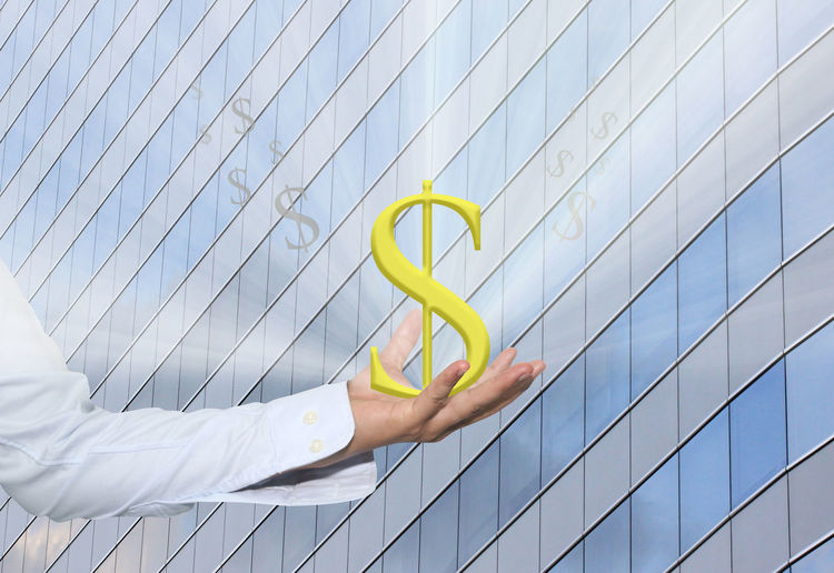 Digital composite image of man holding dollar sign against building with shadows