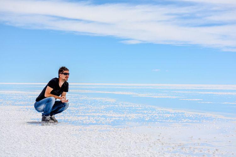 Full length of man crouching on dessert against sky