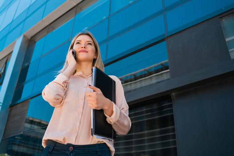 Low angle view of young woman standing against building in city
