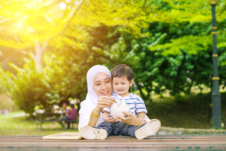 Young woman with her cute son learn how to put coins into piggy bank. Future planning concept. Child Childhood Togetherness Family Males  Men Bonding Son Innocence Two People Boys Sitting Emotion Offspring Casual Clothing Smiling Portrait Happiness Tree Looking At Camera Plant Positive Emotion Outdoors