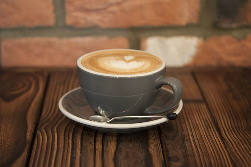 Coffee taken on a wooden table and brick background Cappuccino Close-up Coffee - Drink Coffee Cup Drink Focus On Foreground Food And Drink Froth Art Frothy Drink Latte Mocha No People Refreshment Saucer Table
