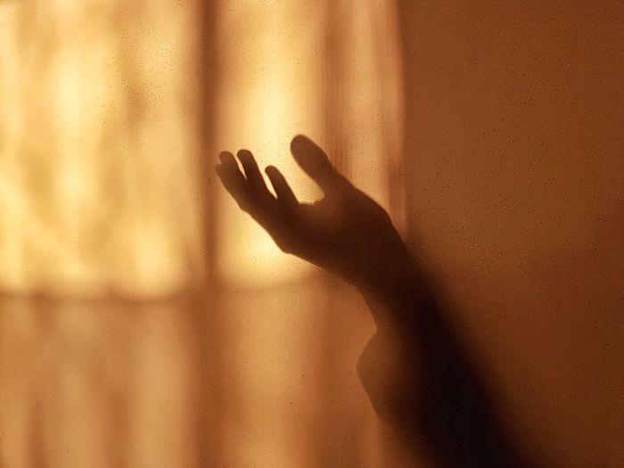 Red zone italia day twentyone - shadow of person hand on glass window against wall