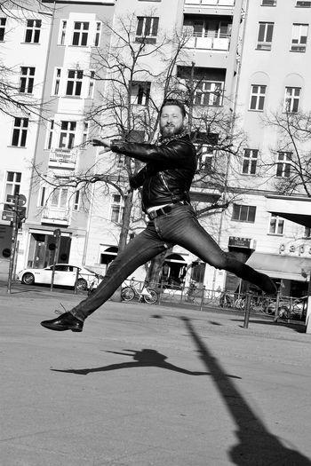 Full length of man jumping on street in city
