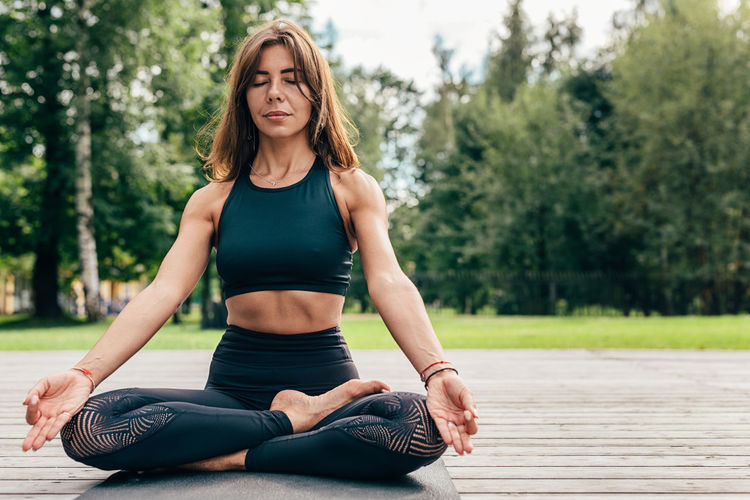 Lifestyles Leisure Activity Real People One Person Yoga Outdoors Exercising Day Training Beautiful Mat Sport Clothes Stretching Healthy Lifestyle Wellbeing Relaxation Exercise Front View Meditating Young Females Body Conscious Lifestyle