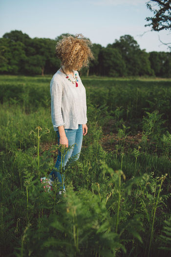 Woman Standing Amidst Plants On Field