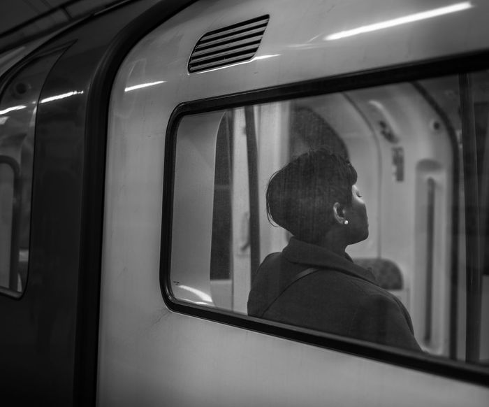 SIDE VIEW OF YOUNG WOMAN SITTING IN TRAIN