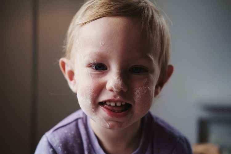 Close-up portrait of smiling cute baby boy with flour on face