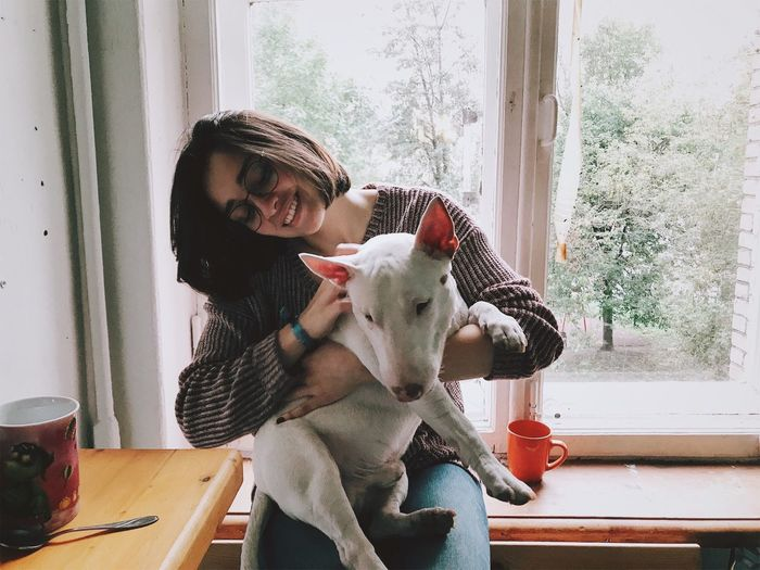Smiling woman with dog sitting at window