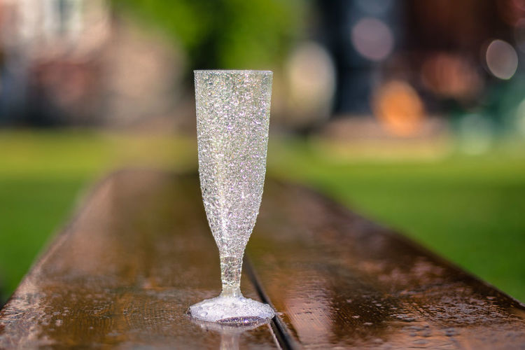 Close-Up Of Champagne Flute On Wet Wooden Bench
