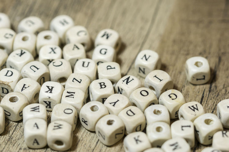 Arts Culture And Entertainment Close-up Communication Cube Shape Dice Gambling Game Of Chance High Angle View Indoors  Large Group Of Objects Leisure Activity Leisure Games Luck No People Number Relaxation Selective Focus Still Life Table Text Wood - Material