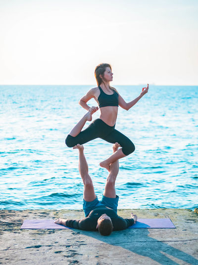 Couple Doing Yoga By Sea