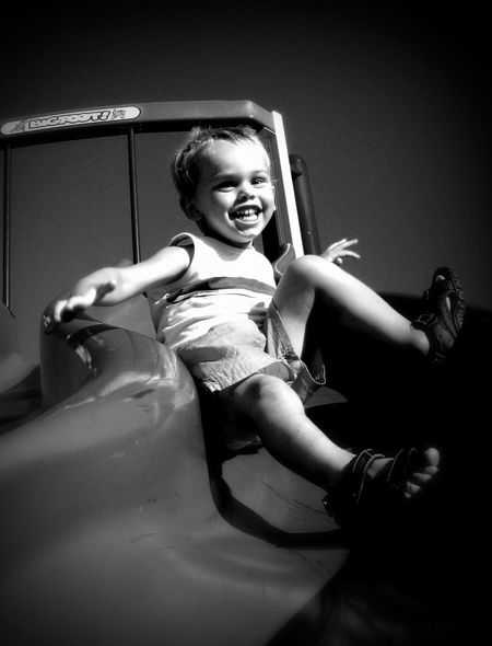 Grandson playing in park. Childhood Day Enjoyment Excitement Fun Lifestyles Mike Stouffer One Person Outdoors Portrait Real People Sitting Slide - Play Equipment Smiling TheSixthLens Water Slide Welcome To Black The Portraitist - 2017 EyeEm Awards The Portraitist - 2017 EyeEm Awards