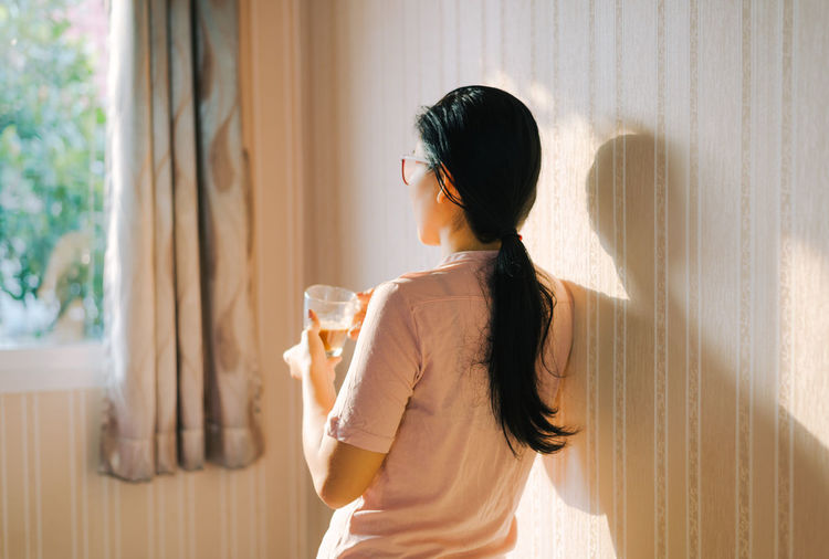 Rear View Of Woman Holding Tea Cup At Home