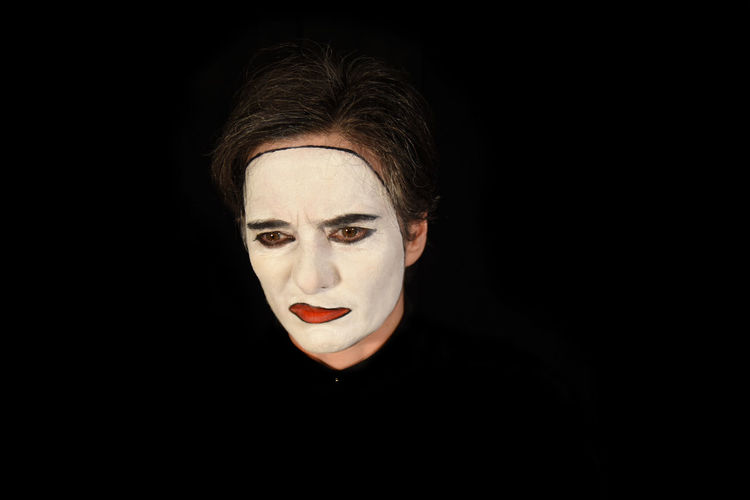 Sad man with face paint against black background