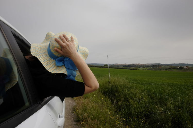 woman with hat looks out of the car window One Person Mode Of Transportation Transportation Car Grass Plant Real People Sky Leisure Activity Motor Vehicle Day Land Vehicle Nature Casual Clothing Field Holding Land Outdoors Green Color Hat Freedom Woman