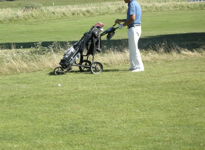 Low section of man with golf bag on field