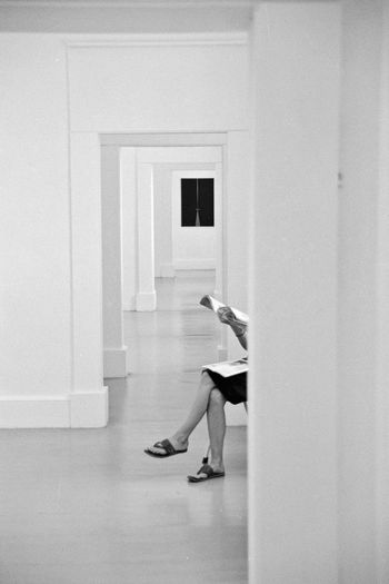 Low Section Of Woman With Magazine Sitting In Corridor