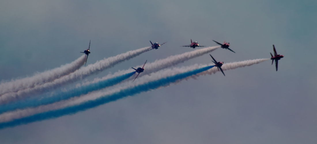 Low angle view of fighter planes performing airshow in sky