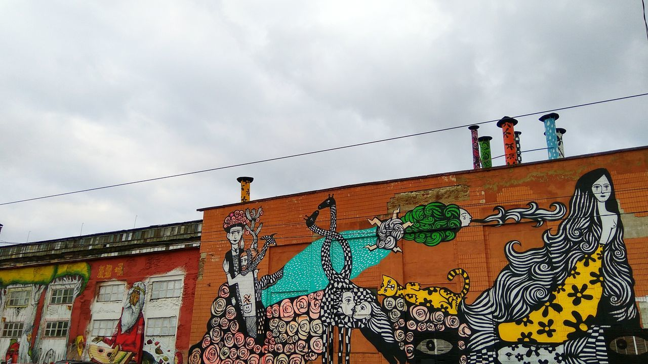 graffiti, low angle view, sky, architecture, built structure, outdoors, day, building exterior, cloud - sky, real people