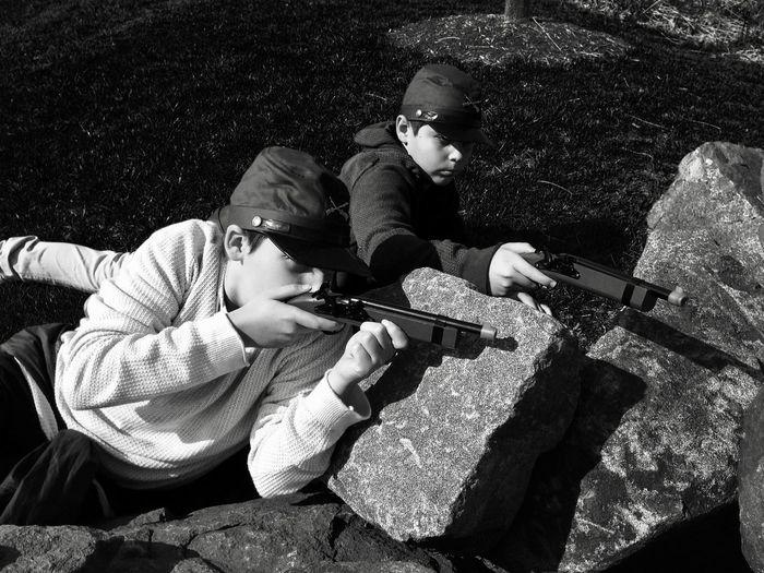 Boys Shooting With Toy Handguns On Rocks