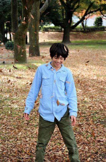 Smiling Boy Standing On Field During Autumn