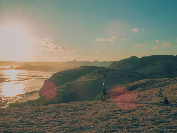 Man standing on hill by sea against sky during sunset