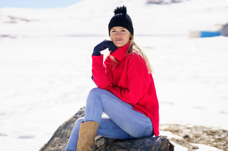 Young woman sitting on rock at beach during winter