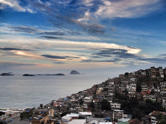 High angle view of slum by sea against sky during sunset