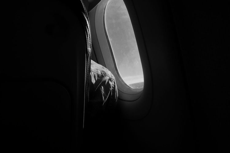 Midsection of man by window in airplane