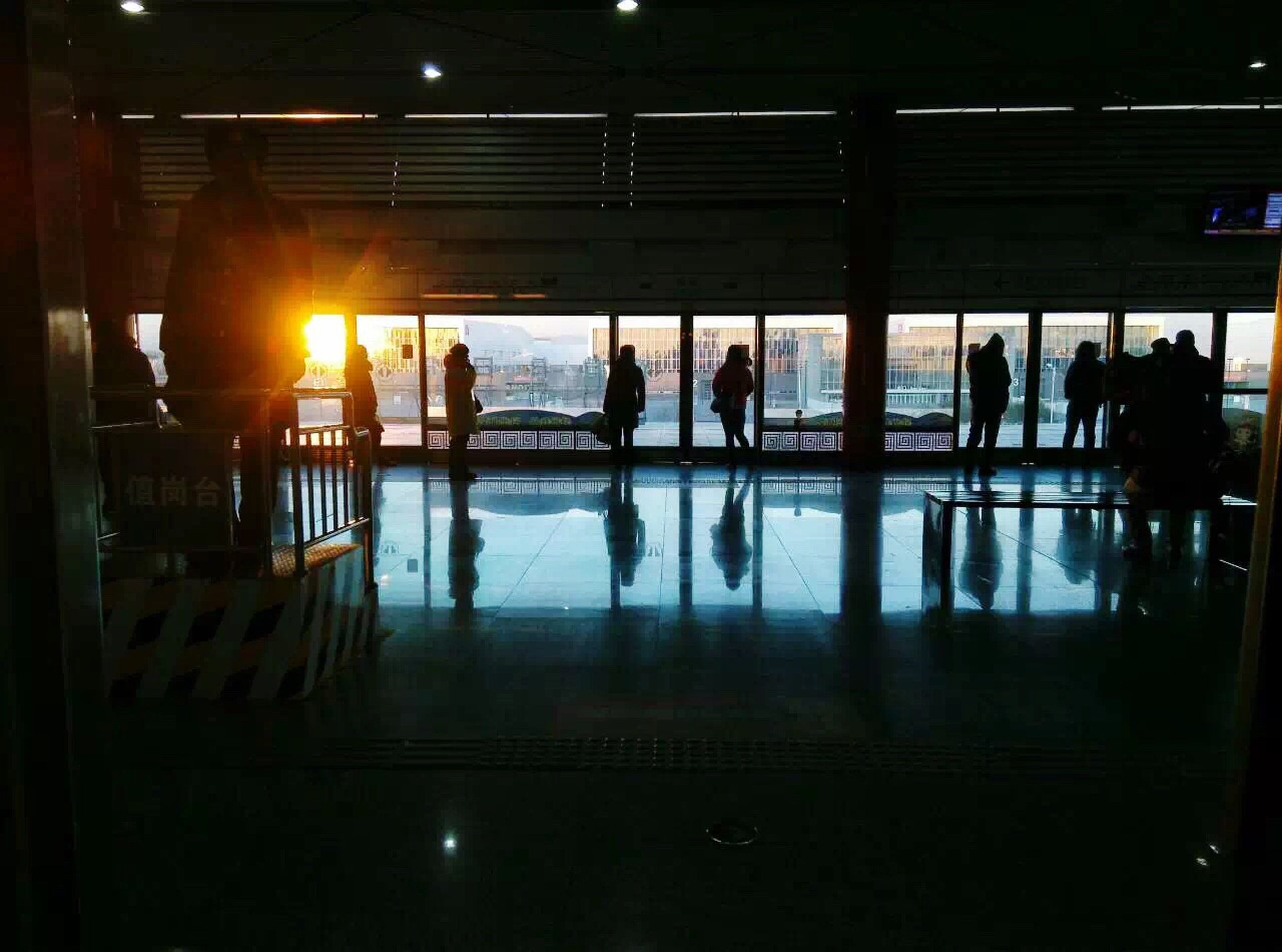 indoors, men, illuminated, architecture, lifestyles, built structure, large group of people, person, railroad station, reflection, silhouette, public transportation, airport, medium group of people, travel, sunset, walking, railroad station platform, transportation