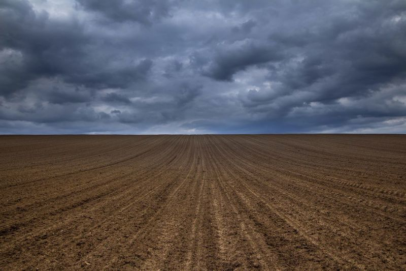 Plowed Field Against Cloudy Sky