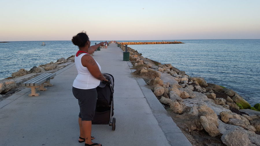 Side View Of Woman With Baby Carriage Pointing Away At Pier Over Sea