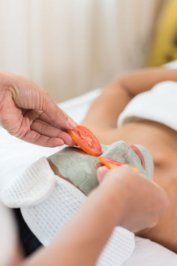 Cropped hands of beautician adjusting tomato slices on woman eyes during facial mask