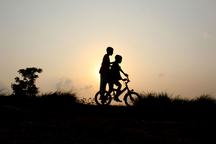 Silhouette Of Boys On Bicycle Against Sky During Sunset