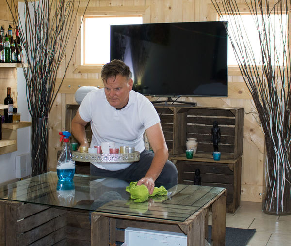 Mature Man Cleaning Table At Home