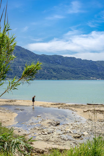 Mid distance of woman walking at beach against mountains