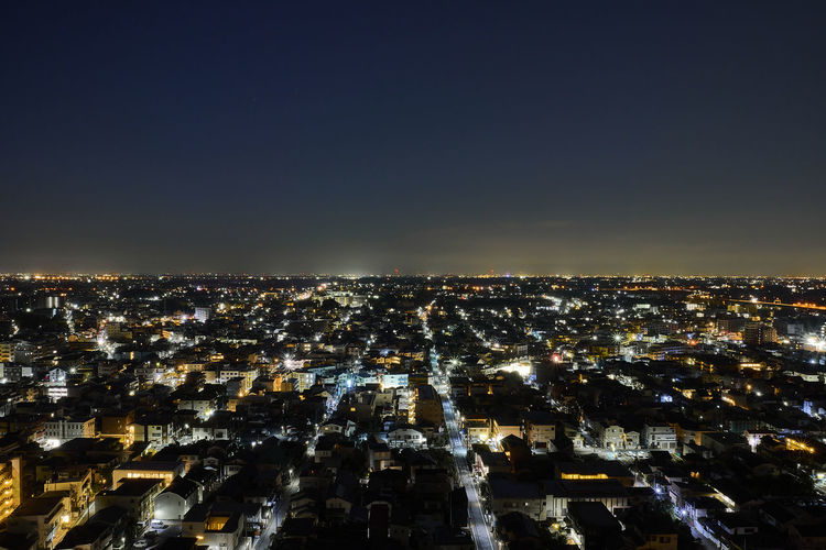 High angle view of illuminated city against clear sky at night